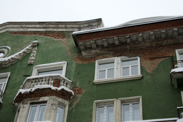 Фасад с обвалившейся штукатуркой.